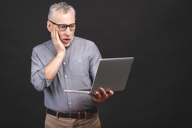 Omg! i'm shocked! scared senior aged bearded old man in eyeglasses holding laptop computer