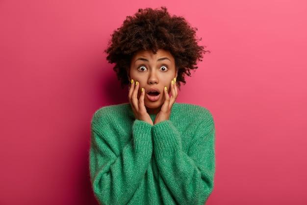 Ой, это ужасно! испуганная безмолвная женщина держит обе руки на щеках, смотрит с вытаращенными глазами, боится чего-то ужасающего, стоит неуверенно, одетая в зеленую одежду, изолирована на розовой стене