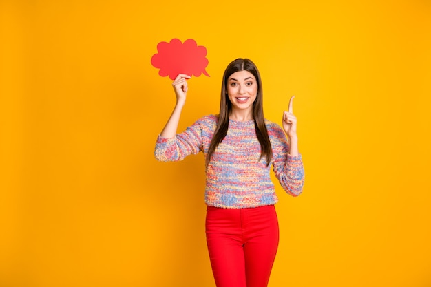 Боже, это невероятно! удивленная девушка держит красную бумажную карточку, пузырь, думает, приходит в голову, поднимает указательный палец, решает решения, выбирает, носить джемпер, изолированный желтый