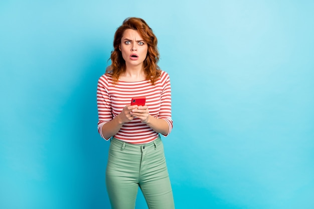Omg its unbelievable! frustrated funny woman use cellphone read horrible social network comments impressed dislike grimace face wear stylish pullover isolated over blue color