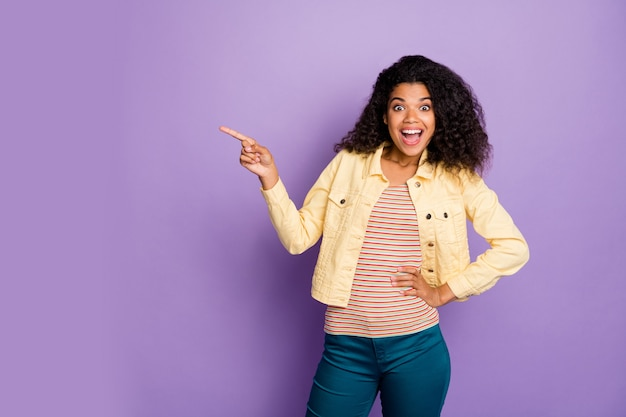 Omg look скидки портрет удивленной сумасшедшей афро-американской девушки указывает указательным пальцем на copyspace указывает невероятную рекламную рекламу в повседневных синих брюках, изолированных на фиолетовом цветном фоне