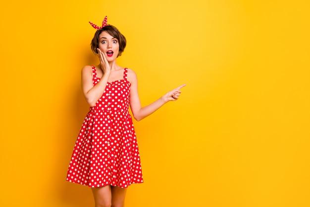 Омг посмотрите невероятные объявления! удивленная сумасшедшая девушка указывает указательный палец copyspace прямо под впечатлением крика прикосновение рук лицо носить винтажную красную юбку оголовье изолированно яркой цветной стены