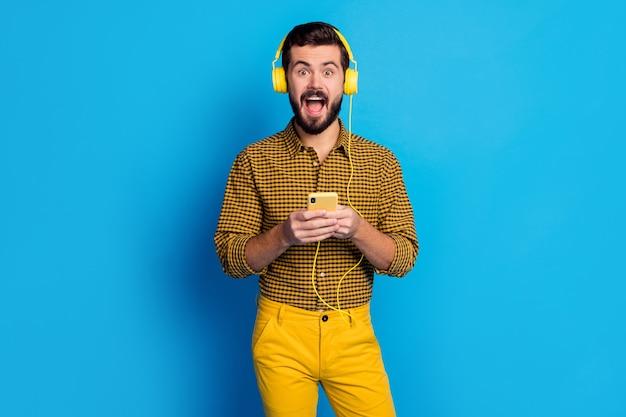 Omg 내가 가장 좋아하는 노래! 놀란 된 흥분된 남자 사용 스마트 폰 검색 스테레오 볼륨 멜로디 비명 들어 음악 착용 헤드셋 체크 무늬 바지 스타일 세련 된 유행 고립 된 파란색