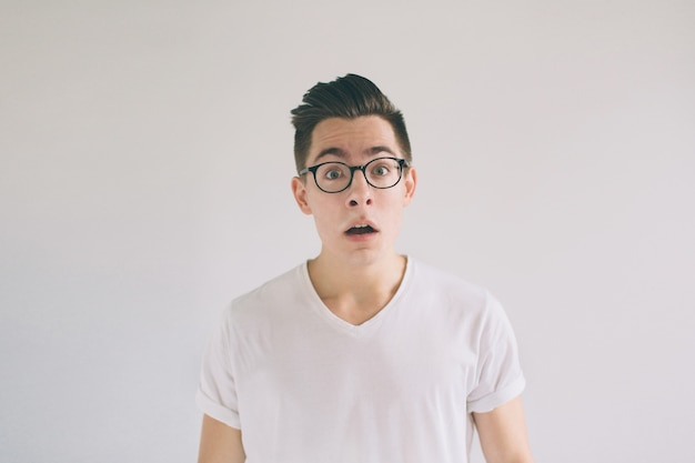 Omg no way very shocked young man with glasses. student nerd is wearing in a white t-shir.