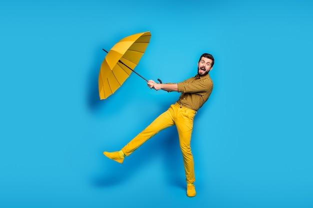 Омг летающий зонтик! полноразмерная фотография сумасшедшего изумленного человека, поймавшего его дождь, защита от ветра, щит, зонтик, крик, одежда, клетчатые брюки, кроссовки, изолированные на синем цвете