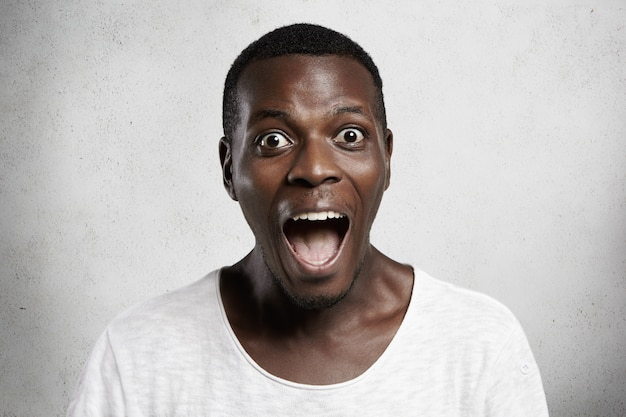 Omg! portrait of astonished wide-eyed african customer in white t-shirt  in surprise and astonishment, shocked with unprecedentedly low prices, screaming with mouth wide open