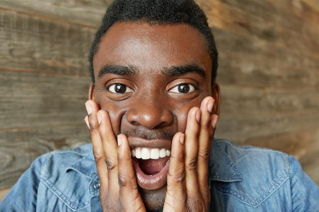 ああ、神様!意外と宝くじに当選した後、ショックを受けて口を大きく開いたまま、頬に手を差し伸べているデニムシャツを着た驚きと驚かれる若いアフリカ人の肖像画。ボディランゲージ