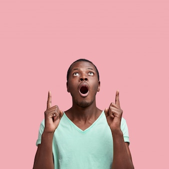 Omg and shock concept. surprised african american male indicates at blank copy space upwads with fore fingers, isolated over pink wall