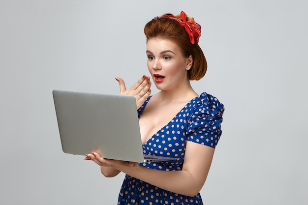 ああ、神様。一般的なラップトップコンピューターを保持し、驚きの表情を持ち、彼女の口に手のひらを保持しているヴィンテージの衣装でゴージャスな感情的な若い女性のスタジオショット