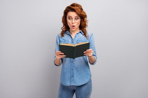 信じられない!驚いたきれいな女性は、灰色の壁に隔離されたスタイリッシュな服を着て、予想外の物語の終わりに感銘を受けた紙の本を読んだ