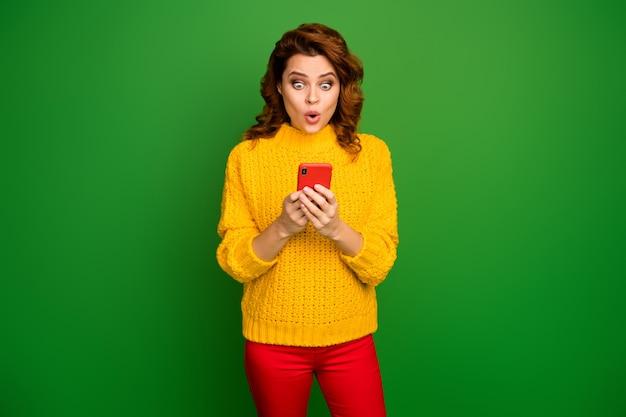 信じられない! astonoshedソーシャルメディアユーザーの女性は携帯電話を使用してオンラインでノベルティに感銘を受けた悲鳴を上げるスタイルのスタイリッシュなジャンパーを明るい輝きの色の壁に分離しました