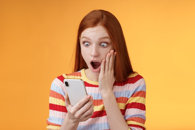 Omg what heck. portrait shocked concerned young redhead sensitive impressed redhead woman stare smartphone display touch cheek drop jaw stunned surprised standing orange background hold phone.