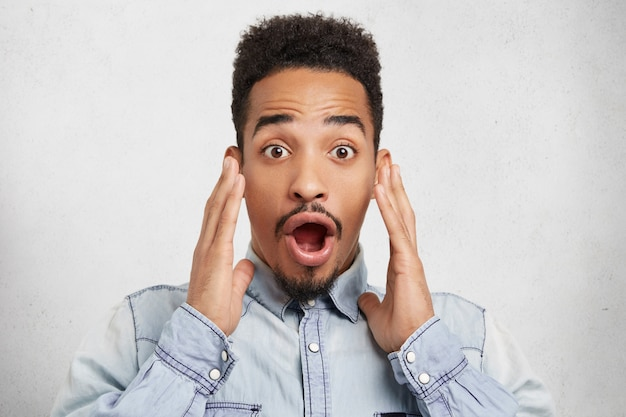 Omg, what i see! african astonished man has shocked expreesion, looks with wide open eyes and mouth