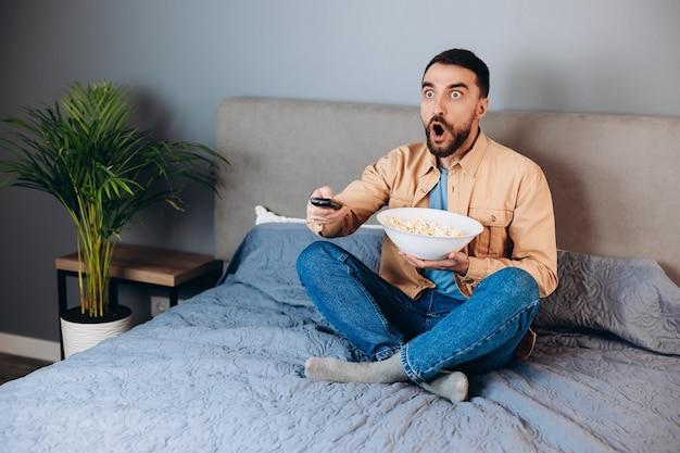 Омг, что это такое. удивленный человек в карантине, свободное время, смотреть фильм, удивленный, неожиданный финал триллера, подержать большую коробку с попкорном, сидеть на диване в доме, в помещении.