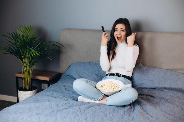 Омг, что это такое. кричит испуганная женщина. симпатичная женщина в карантине, свободное время, смотреть фильм, впечатлена, удивлена неожиданным окончанием триллера, подержать большую коробку с кукурузой, сидеть на диване в доме, в помещении.