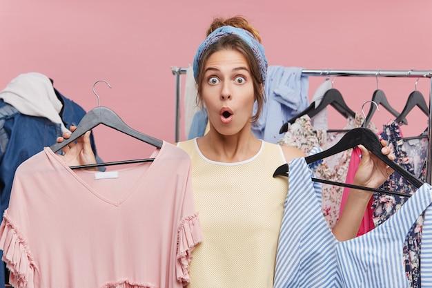 Ого, вау. взволнованная молодая европейская шопоголика, ищущая одежду в магазине, шокированная ценами продажи, держащая две вешалки с розовыми и синими платьями, стоящая у стойки, полной разноцветных вещей