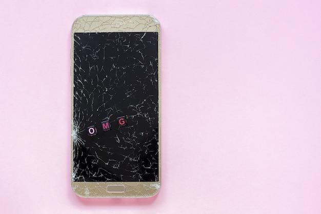 ピンクの背景に壊れた携帯電話とテキストomg