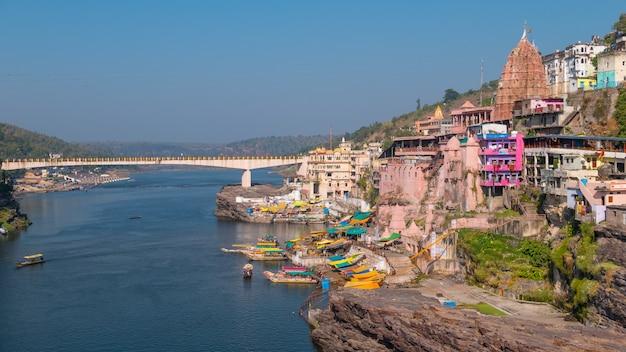 Omkareshwar cityscape, india, sacred hindu temple. holy narmada river, boats floating.