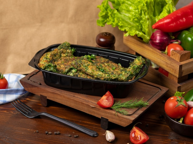 Omlette takeaway with herbs and vegetables in black container.