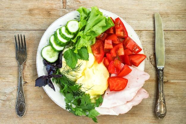 Омлет с помидорами, огурцами, травами, ветчиной и салатом на старом деревянном столе, вилка и нож