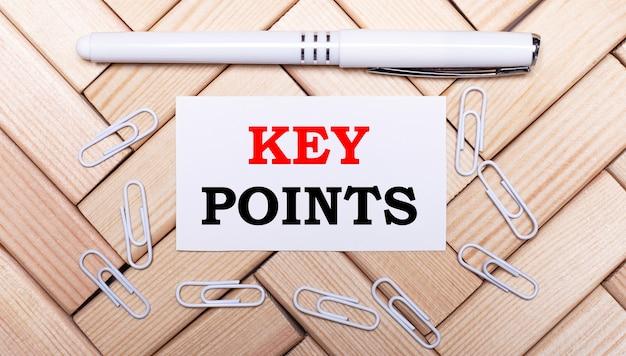 나무 블록, 흰색 펜, 백서 클립 및 텍스트가있는 흰색 카드의 배경에 key points