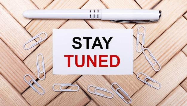 На фоне деревянных блоков белая ручка, белые канцелярские скрепки и белая карточка с надписью stay tuned. вид сверху