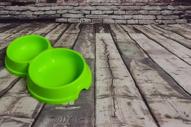 木製の灰色のボードの背景に猫や犬を養うための空の緑色のプラスチックプレートがあります