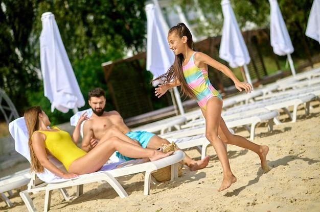 На пляже. родители и девочка на пляже