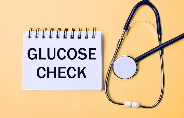 На бежевом фоне стетоскоп и белый блокнот с надписью glucose check. медицинская концепция Premium Фотографии
