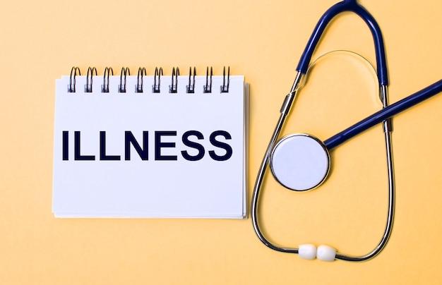 ベージュの背景に、聴診器とillnessの刻印が入った白いメモ帳。医療の概念