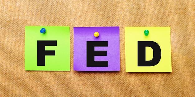 На бежевом фоне разноцветные наклейки для заметок со словом fed.