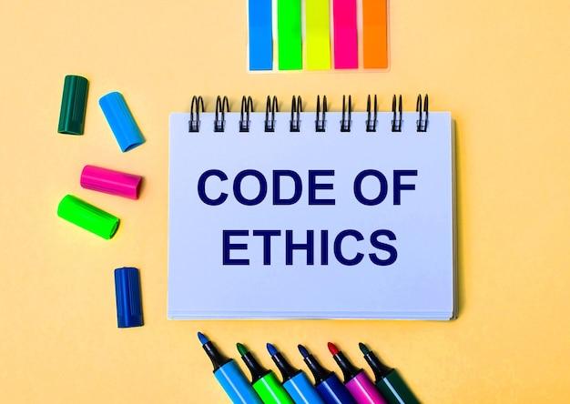 ベージュの表面に、code of ethicsという言葉が書かれたノート、明るいフェルトペンとステッカー