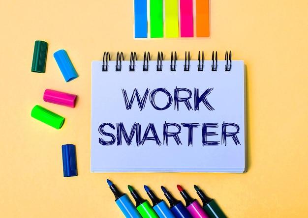 베이지 색 표면에 work smarter라는 문구가 적힌 노트북, 밝은 펠트 펜 및 스티커