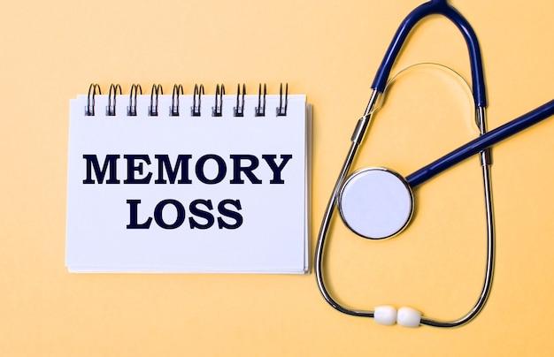 베이지 색 표면에는 청진기와 memory loss라는 비문이있는 흰색 메모장이 있습니다. 의료 개념