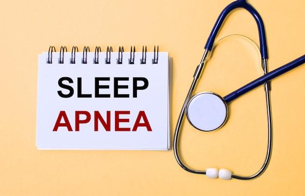 На бежевой поверхности стетоскоп и белый блокнот с надписью sleep apnea. медицинская концепция