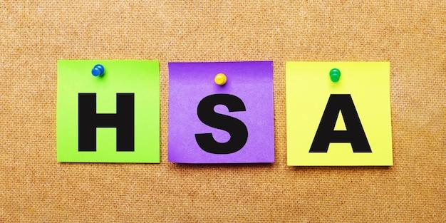 На бежевой поверхности разноцветные наклейки для заметок со словом hsa.