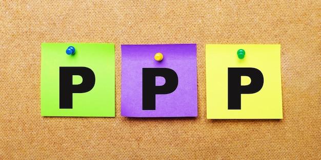 На бежевой поверхности разноцветные наклейки для заметок со словом ppp paycheck protection program.