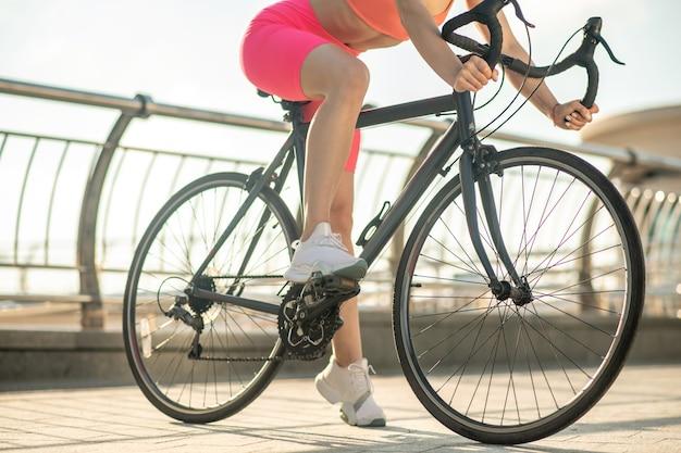 自転車に乗って。自転車に乗っている女性サイクリストの写真をクローズアップ