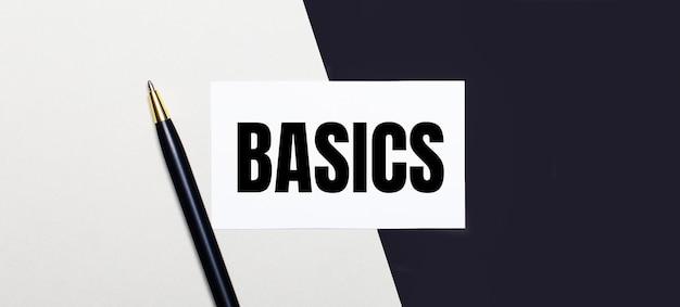 黒と白の背景にペンとテキストbasicsの白いカードがあります