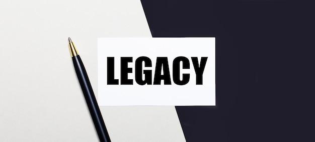 На черно-белом фоне лежит ручка и белая карточка с текстом наследие.