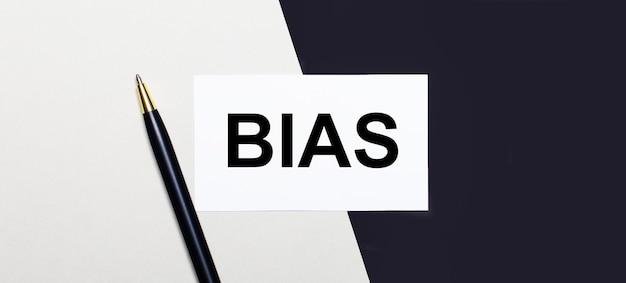 흑백 표면에 bias라는 텍스트가있는 펜과 흰색 카드가 있습니다.