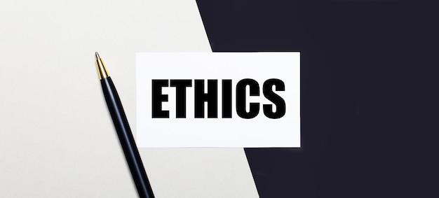 흑백 표면에는 ethics라는 텍스트가있는 펜과 흰색 카드가 있습니다.
