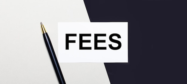 黒と白の表面には、「fees」というテキストが書かれたペンと白いカードがあります。