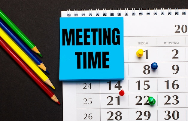 黒の背景に、色付きのボタン、マルチカラーの鉛筆、meetingtimeの刻印が入った青いステッカーが付いたカレンダー。