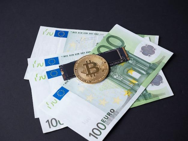 검정색 배경에는 유로 지폐, m2 ssd 디스크 및 비트코인이 있습니다. 하드 디스크에 대한 마이닝의 개념입니다. 암호화폐.