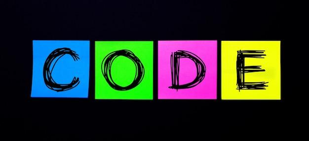 黒の背景に、codeという言葉が書かれた明るい色とりどりのステッカー。図