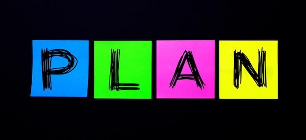 На черном фоне яркие разноцветные наклейки со словом план.
