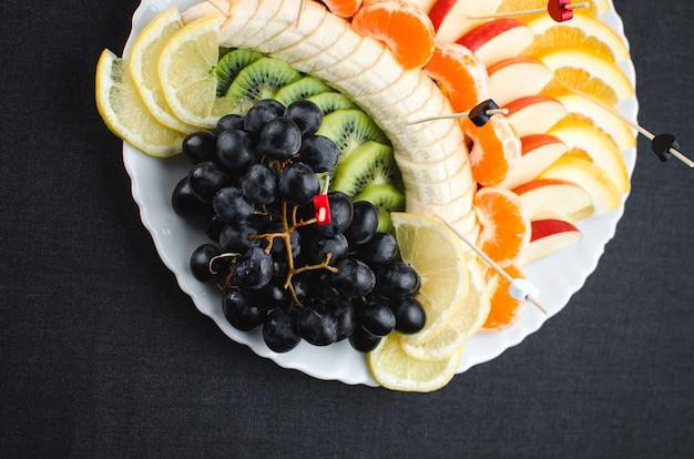 흰색 접시 과일 슬라이스의 검은 배경에 아름답게 배치