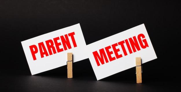 木製の洗濯ばさみの黒い背景に、「親の会議」というテキストが付いた2枚の白い空白のカード