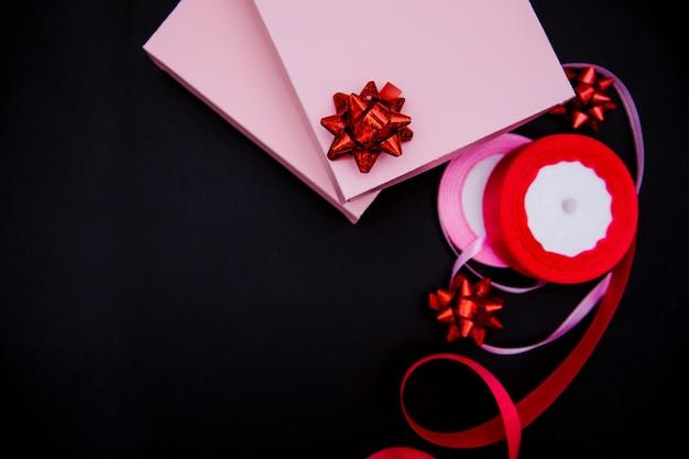 На черном фоне розовые подарочные коробки. рядом - розовые атласные ленты и подарочные бантики. подарочная упаковка. концепция 8 марта и дня святого валентина.